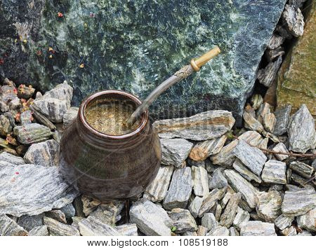 Yerba mate in a traditional calabash gourd and bombilla on the rock horizontal