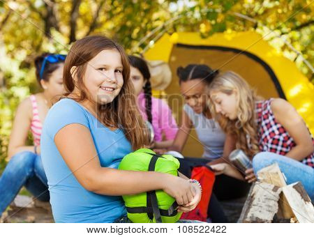 Cute girl holds sleeping bag sitting near camp