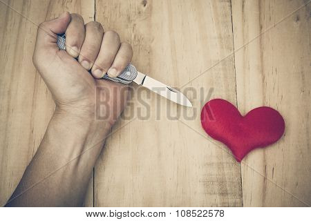 hand with a knife stabbing into a red heart