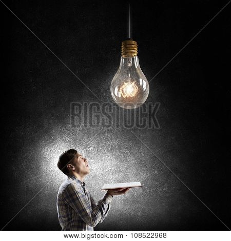Young man holding opened book and glass glowing bulb hanging above