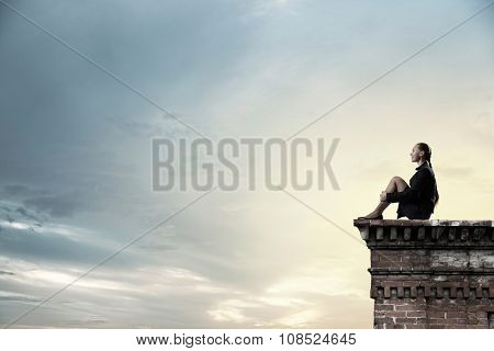 Bored young businesswoman sitting alone on building top