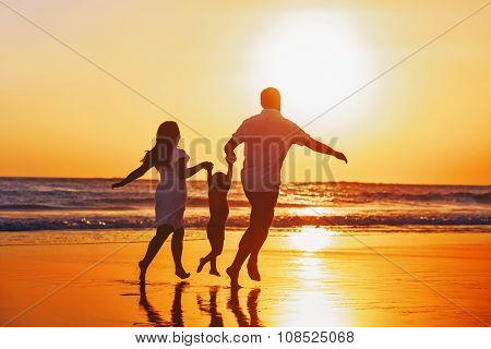 Happy Family With Child Have A Fun On Sunset Beach