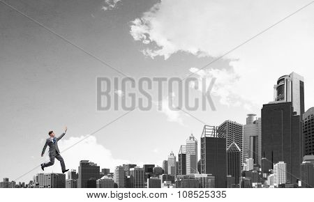 Young businessman running over city buildings and skyscrapers