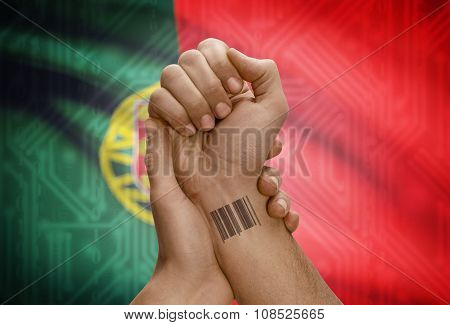 Barcode Id Number On Wrist Of Dark Skinned Person And National Flag On Background - Portugal