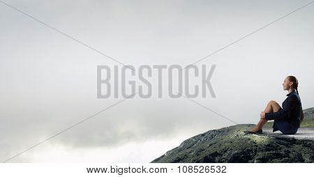 Bored young businesswoman sitting alone on rock top