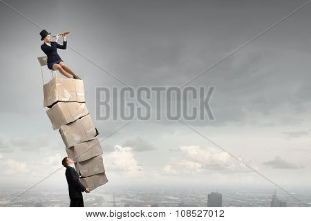 Businesswoman sitting on big stack of carton boxes and looking in spyglass