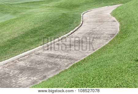 Path Curving Through Green Lawn In Golf Course.