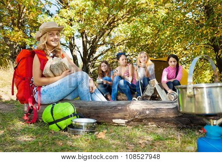 Blond girl holding kindling wood sitting on log