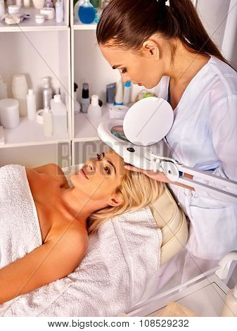 Woman middle-aged lying in spa salon with cosmetic lamp .