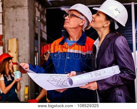 Business woman  and man in builder helmet indoor. Elderly man teaches young girl and look up.