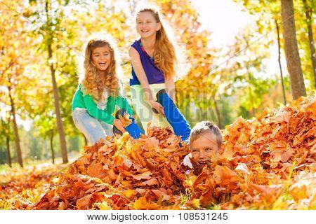 Girls having fun dragging boy laying on the ground