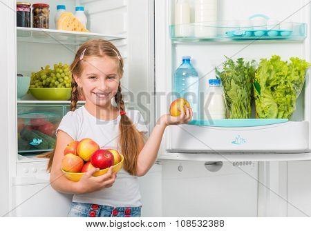 little girl holding apples from an opened fridge