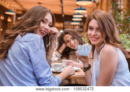 Portrait of a three girlfriends drinking coffee in cafe together