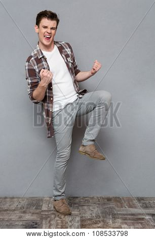 Delighted cheerful handsome positive joyful young man in checkered shirt and gray pants dancing and smiling on gray background