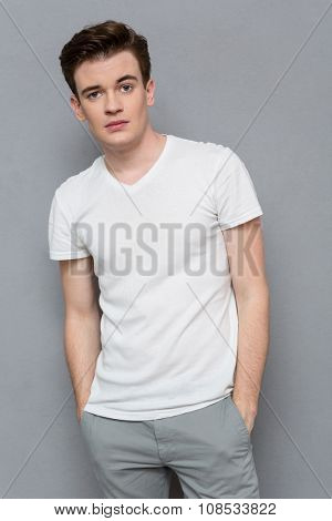 Portrait of confident serious young man in white t-shirt and gray pants on gray background