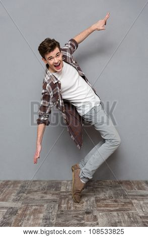 Full length portrait of excited happy cheerful positive handsome dancing young man in plaid shirt isolated on white background