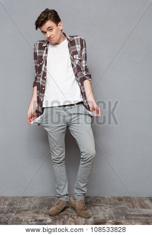 Full length portrait of a casual man exhibiting his empty pockets on gray background
