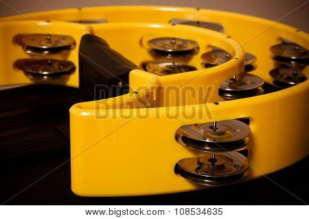 the single yellow tambourine on black background.