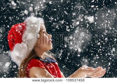 a Christmas miracle! happy little girl catching snowflakes in her hands