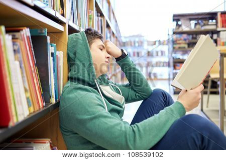 people, knowledge, education, literature and school concept - student boy or young man sitting on floor reading book in library
