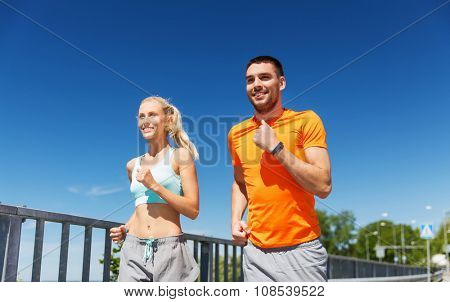 fitness, sport, friendship and healthy lifestyle concept - smiling couple with heart-rate watch running at summer seaside