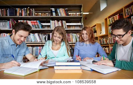 people, knowledge, education and school concept - group of happy students writing to notebooks in library