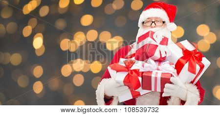 christmas, holidays and people concept - man in costume of santa claus with gift boxes over golden lights background