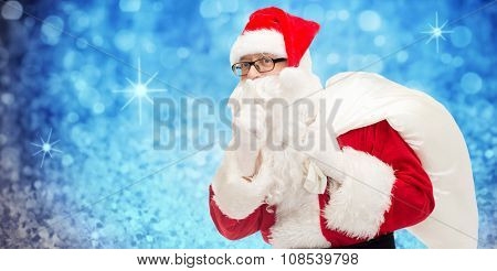 christmas, holidays and people concept - man in costume of santa claus with bag making hush gesture over blue glitter or lights background