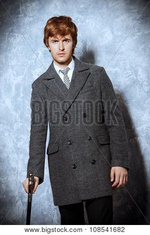 Handsome man in an elegant coat. Beauty, fashion. Studio shot.