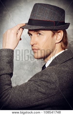 Close-up portrait of a handsome man in an elegant hat. Beauty, fashion. Studio shot.