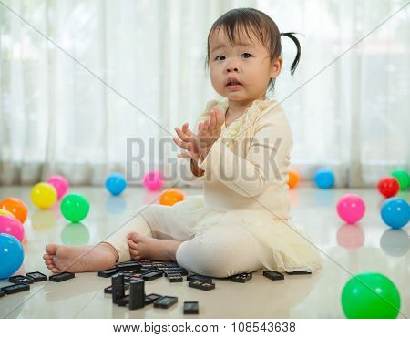 Little Girl Playing With Black Domino