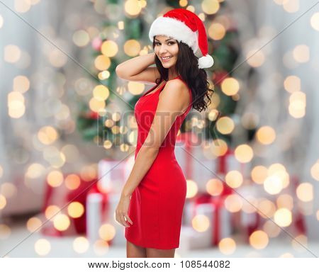 people, holidays, christmas and celebration concept - beautiful sexy woman in santa hat and red dress over christmas tree lights and presents background