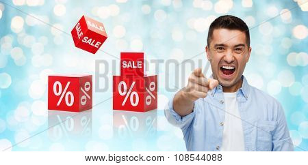 shopping, sale, discount, gesture and people concept - angry man shouting and pointing finger on you over blue holidays lights and red percentage signs background