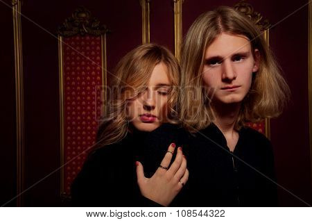 Couple Of Young Blond People Dressed In Black In A Dark Room