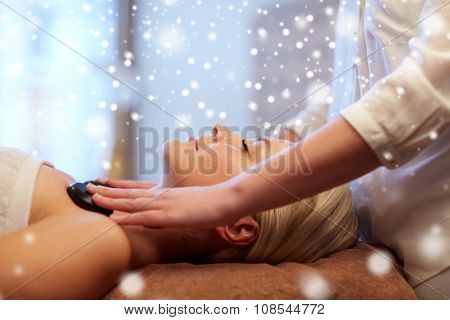 people, beauty, spa, healthy lifestyle and relaxation concept - close up of beautiful young woman having hot stone massage in spa with snow effect
