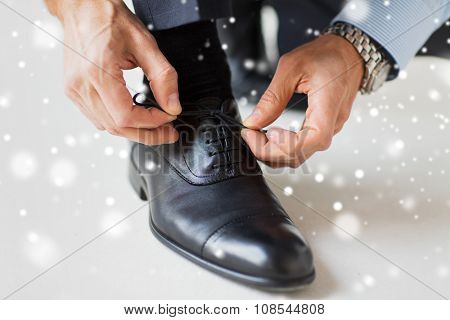 people, business, fashion and footwear concept - close up of man leg and hands tying shoe laces over snow effect