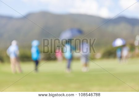 Blurred Photo Of Golfer In Green Golf Course.
