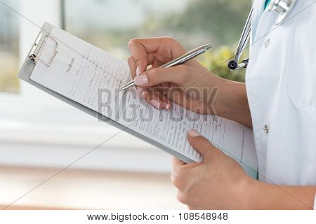 Close-up View Of Female Doctor Hands Filling Patient Registration Form