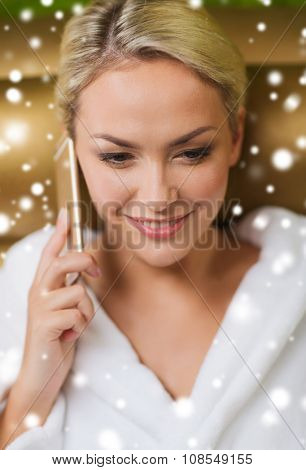 people, beauty, lifestyle, technology and relaxation concept - beautiful young woman in white bath robe with smartphone calling and talking at spa with snow effect