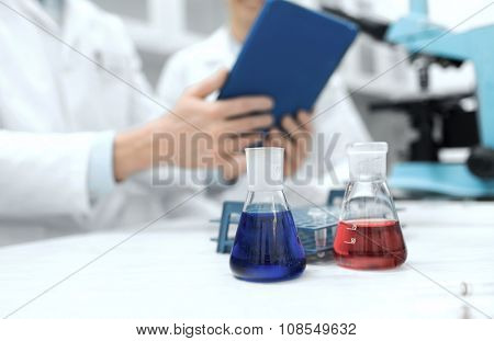 science, chemistry, technology, biology and people concept - close up of scientists with glass tes flasks and tablet pc computer on table in lab