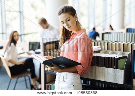 Beautiful Woman Reading A Book In A Library