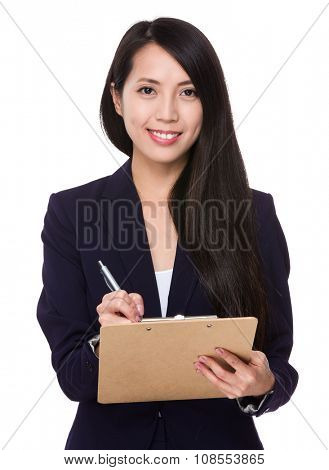 Asian Young Businesswoman write on clipboard