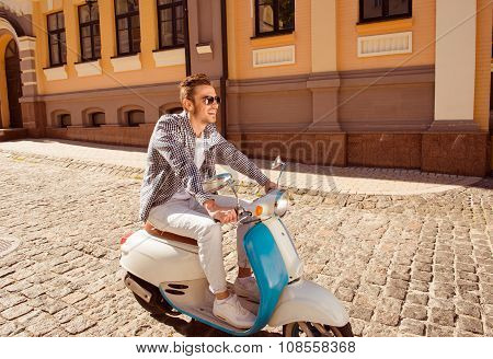 Beautiful Cheerful Man With Sunglasses Riding A Scooter