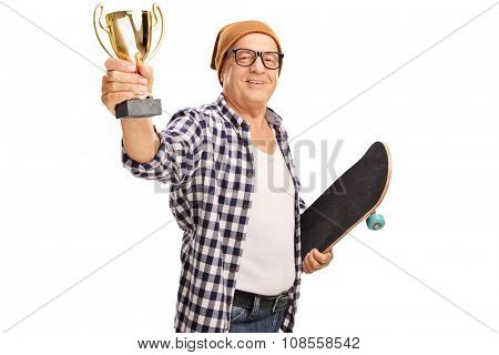 Mature skater holding a skateboard and a golden trophy isolated on white background