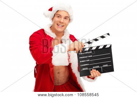 Young man in a Santa costume posing with unbuttoned shirt and holding a movie clapperboard isolated on white background