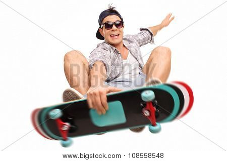 Young male skater performing tricks with his skateboard shot in mid-air isolated on white background