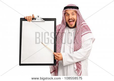 Young excited Arab holding a clipboard with a blank paper and pointing on it with a wooden stick isolated on white background