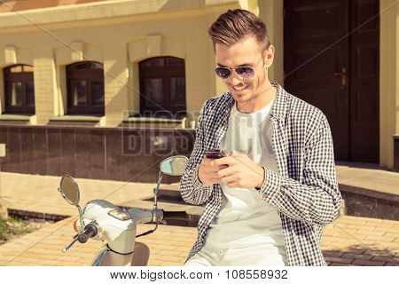 Handsome Happy Man Sitting On The Motorbike Typing A Message On The Phone
