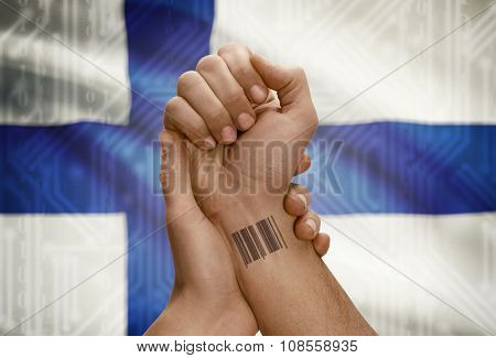 Barcode Id Number On Wrist Of Dark Skinned Person And National Flag On Background - Finland