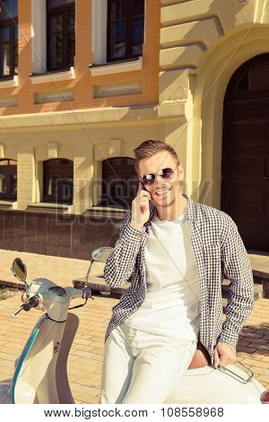 Young Handsome Man Sitting On The Motorbike Talking On The Phone